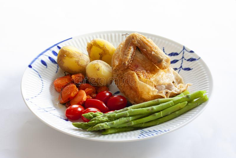 Pollo arrostito al forno con i pomodori di prugna, le patate novelle e l'asparago verde su un piatto Vista superiore su fondo di  fotografie stock libere da diritti