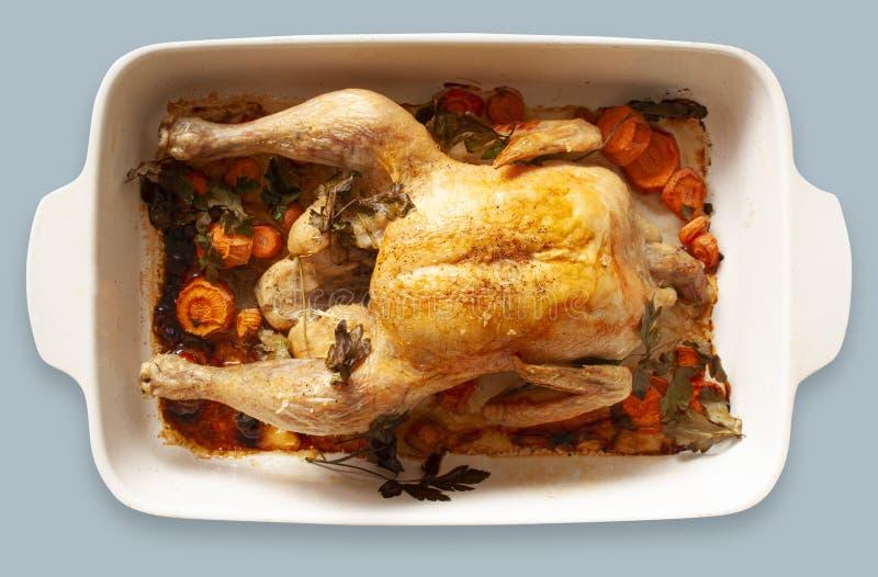 Pollo arrostito al forno con le verdure in un piatto bollente Immagine di vista superiore su fondo grigio blu-chiaro immagine stock