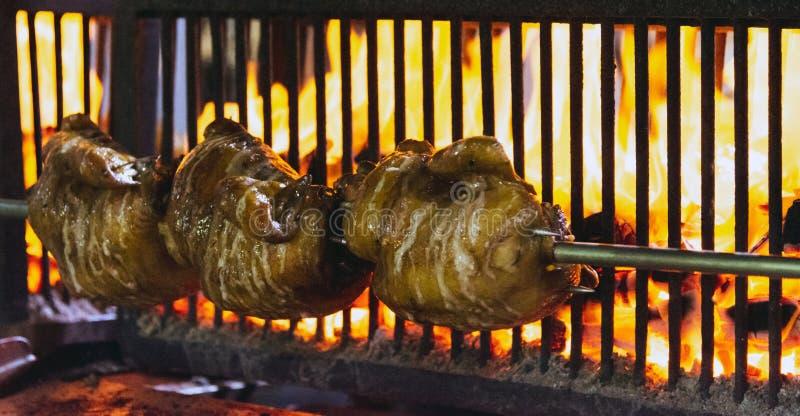 Pollo arrostito che cucina sulla griglia calda ardente fotografie stock