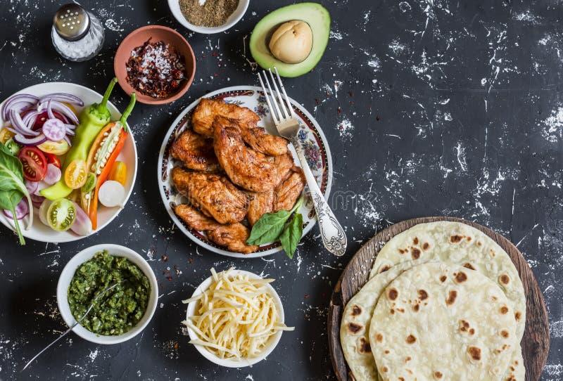 Pollo arrostito piccante, tortiglia, avocado, formaggio, verdure su un fondo scuro fotografia stock