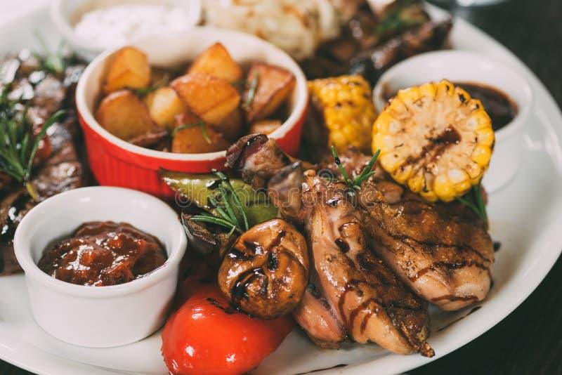 pollo arrostito saporito con le patate, il mais, i funghi e la salsa fritti immagini stock