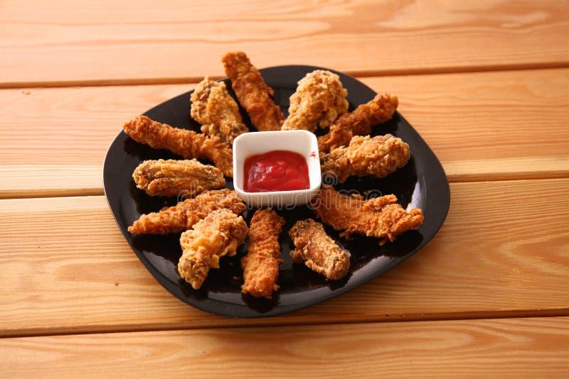 Pollo arrostito su un piatto che sta la tavola di legno fotografia stock