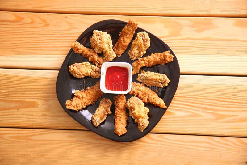 Pollo arrostito su un piatto che sta la tavola di legno fotografie stock