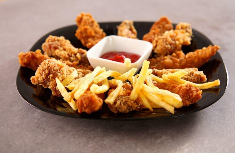 Pollo arrostito su un piatto che sta la tavola di legno immagine stock