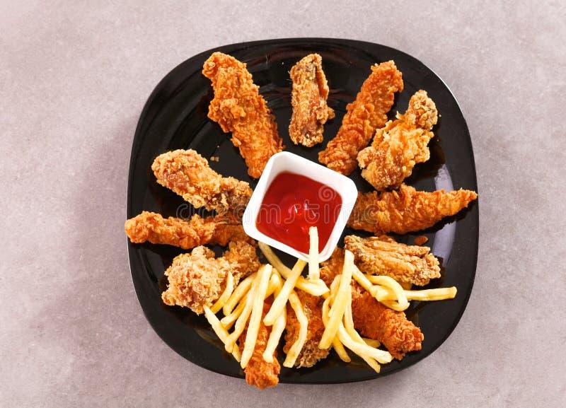 Pollo arrostito su un piatto che sta la tavola di legno fotografia stock libera da diritti
