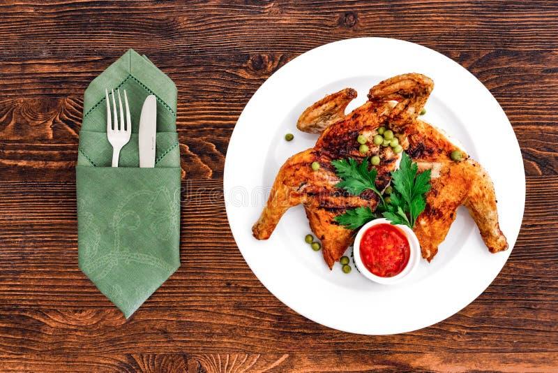 Pollo arrosto fritto grigliato Tabaka su un piatto su un fondo di legno, vista superiore con gli apparecchi fotografia stock