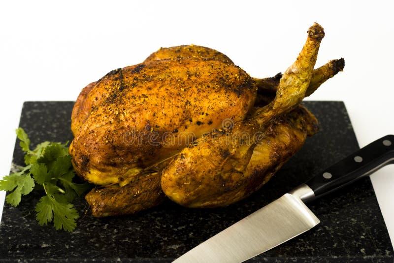 Pollo asado y coriandro en tajadera fotografía de archivo