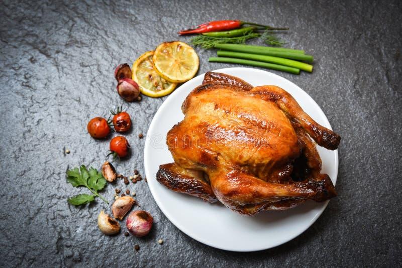 Pollo asado en la placa/pollo entero cocido asados a la parrilla con en las hierbas y especias y fondo oscuro imagenes de archivo