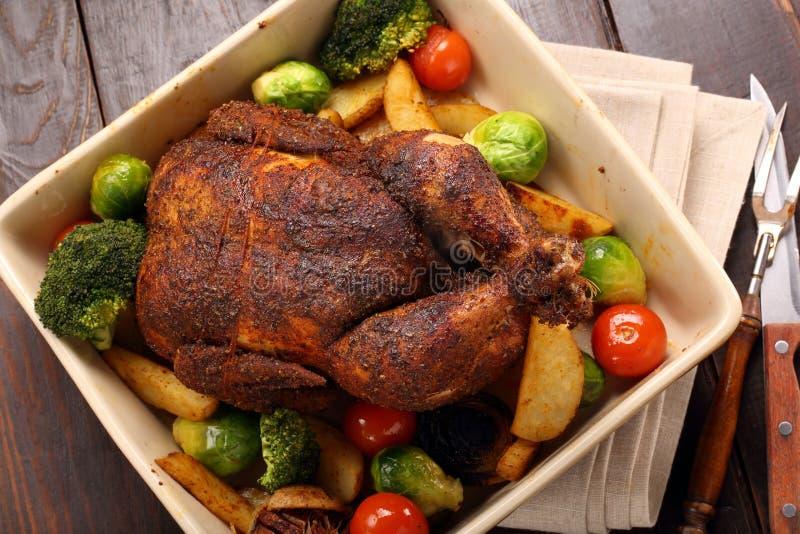 Pollo asado entero con las verduras en cuenco imagen de archivo