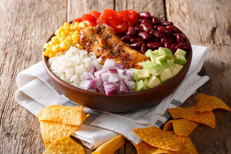 Pollo asado a la parrilla con el arroz, aguacate, habas, tomates, maíz y encendido fotografía de archivo