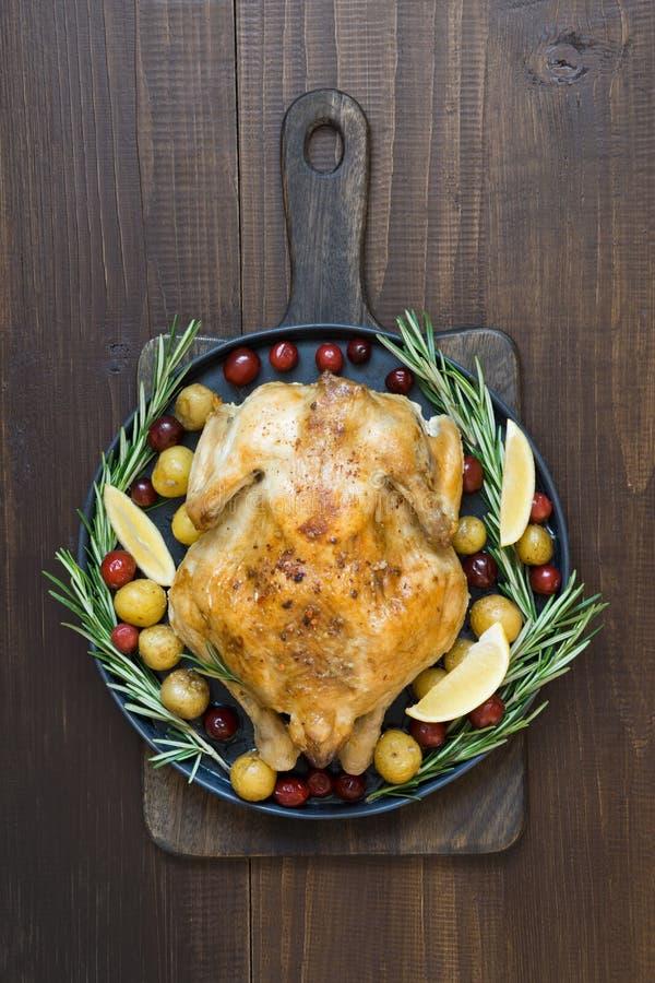 Pollo asado tradicional con romero en la tabla de madera Visión superior fotos de archivo