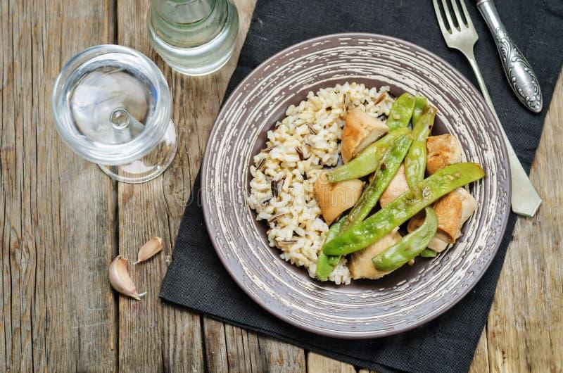 Pollo balsámico con las habas verdes y el arroz moreno fotografía de archivo