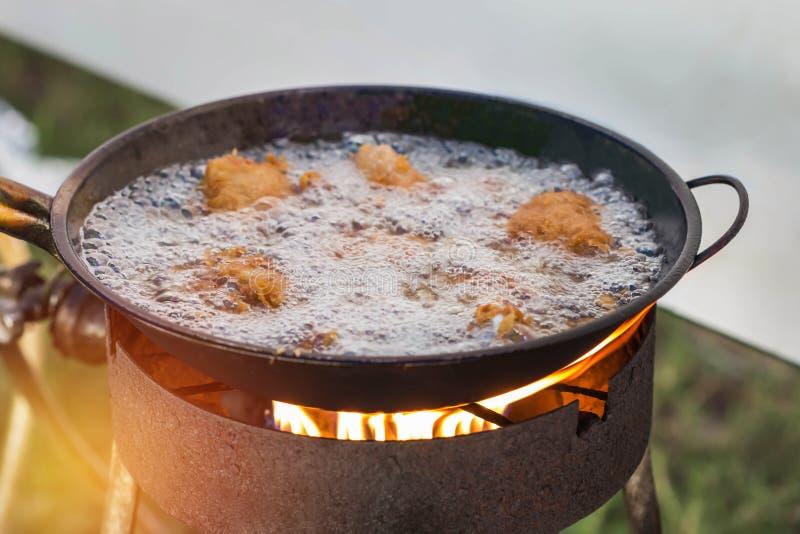 Pollo che frigge con l'olio caldo nella pentola fotografia stock