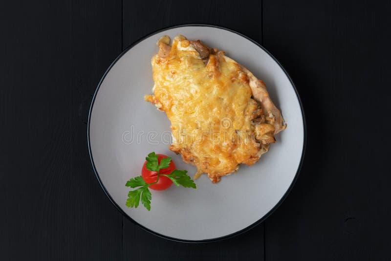 Pollo cocido debajo del queso con el tomate y el perejil fotografía de archivo