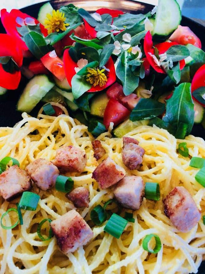 Pollo cocinado casero delicioso de las pastas y ensalada fresca del jardín con verdes de los pétalos y de las naturalezas de la f fotos de archivo