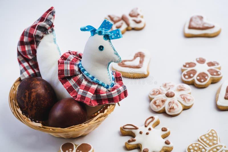 Pollo coloreado del juguete y huevos de Pascua pintados del pollo en una jerarquía de mimbre y las galletas del pan de jengibre,  imágenes de archivo libres de regalías