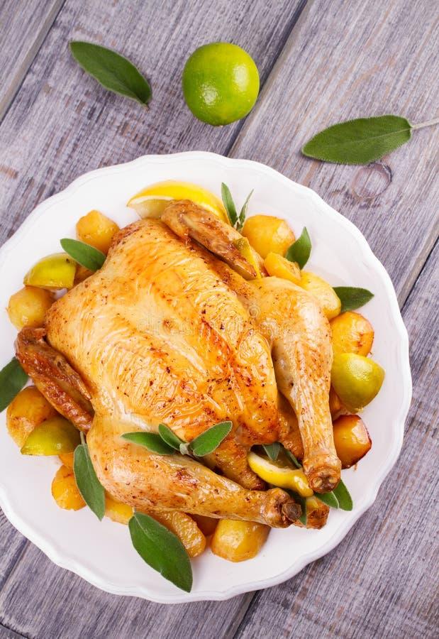 Pollo con el limón, la cal y la patata adornados con sabio fotografía de archivo libre de regalías