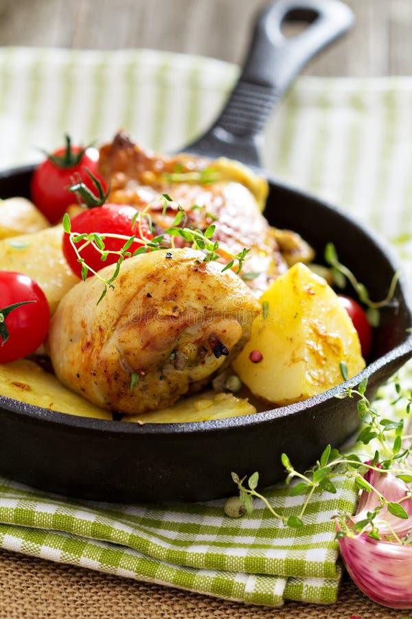 Pollo con las patatas y los tomates frescos fotos de archivo