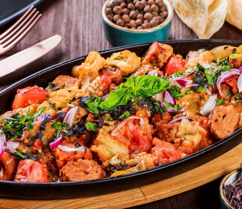 Pollo cotto con le verdure arrostite, verdi, lavash in pentola sulla tavola di legno Piatti caldi della carne immagini stock libere da diritti