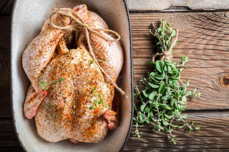 Pollo crudo con las hierbas en plato de la cazuela imagen de archivo libre de regalías