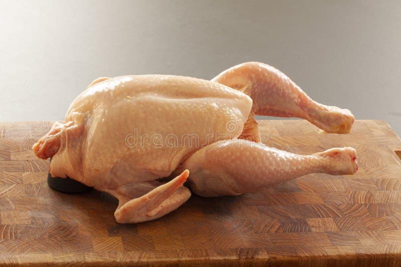 Pollo crudo en una tajadera lista para ser preparado para cocinar Ci?rrese encima de imagen foto de archivo