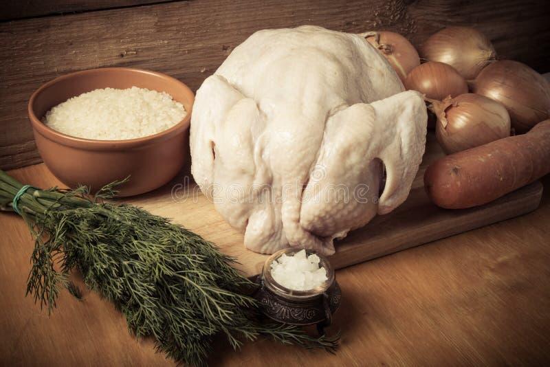 Pollo crudo entero, cebolla, zanahoria, eneldo, arroz, sal en el CCB de madera foto de archivo