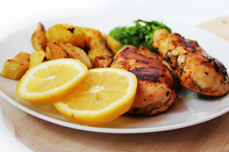 Pollo de carne asada con las patatas cocidas al horno y el verde fotografía de archivo libre de regalías