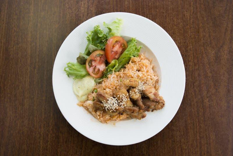 Pollo del arroz frito con la patata y la verdura en el plato blanco en la tabla de madera Goreng asiático del nasi del arroz frit foto de archivo