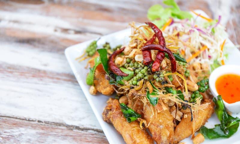 Pollo delizioso e fritto dell'ala con l'erba, pepe, peperoncini rossi, insalata e salsa, alimento tailandese o asiatico famoso immagine stock