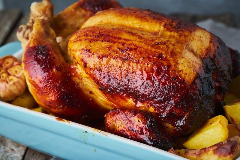 Pollo entero cocido en cazuela azul en la tabla de madera vieja gris oscuro, carne asada con las patatas Vista lateral, cierre pa imágenes de archivo libres de regalías