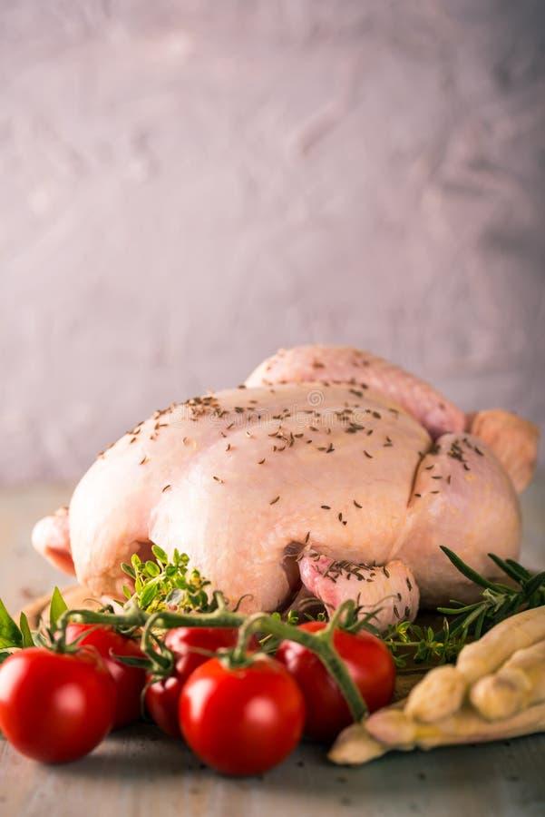 Pollo entero con la especia del comino, el espárrago blanco y los tomates rojos fotos de archivo