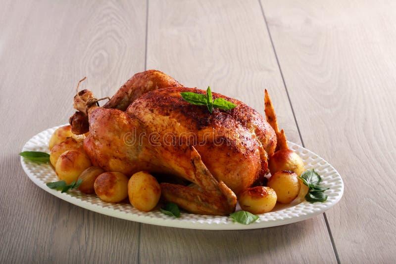 Pollo entero de la carne asada con las patatas imagenes de archivo