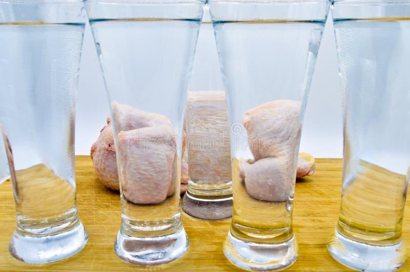 Pollo entero detr?s de los vidrios llenos de agua foto de archivo libre de regalías