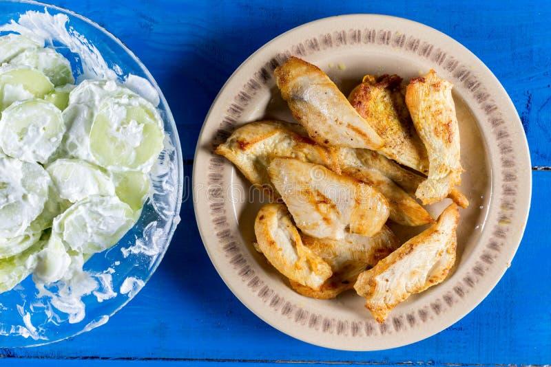 Pollo frito de la endecha plana con la ensalada del pepino sobre fondo de madera azul de los tablones fotografía de archivo libre de regalías