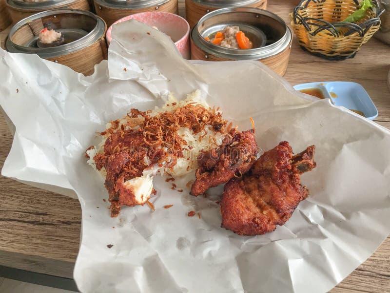 Pollo frito y arroz pegajoso en el abrigo del papel foto de archivo