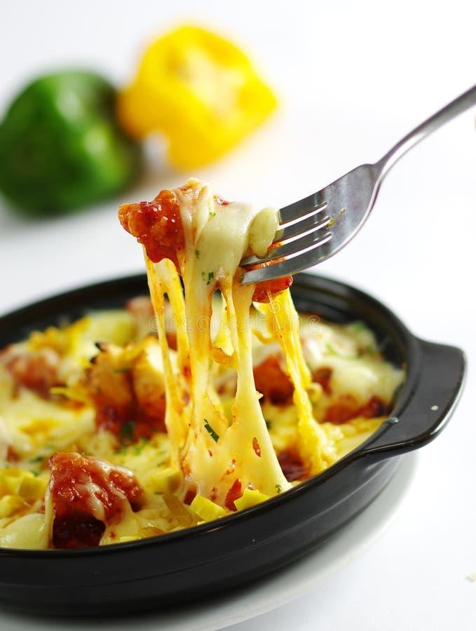 Pollo fritto con formaggio ed il peperoncino rosso in pentola nera nel backgr bianco fotografie stock libere da diritti