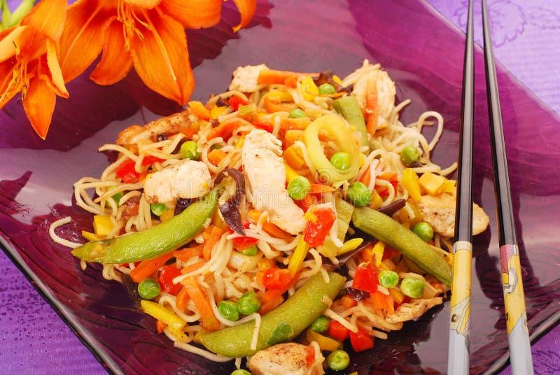 Pollo fritto nel grasso bollente con le verdure e le tagliatelle immagini stock
