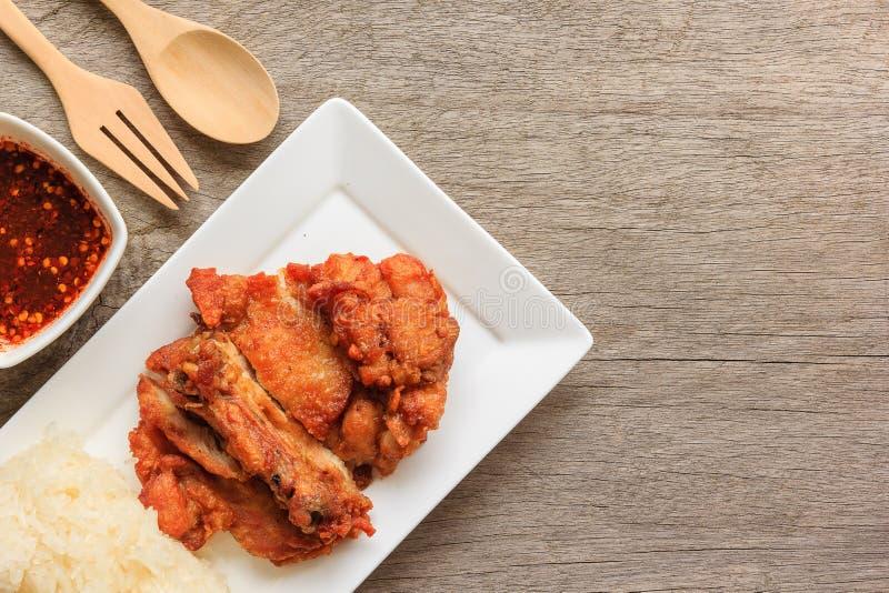 Pollo fritto tailandese di stile con salsa piccante rossa e riso appiccicoso sulla tavola di legno immagini stock libere da diritti