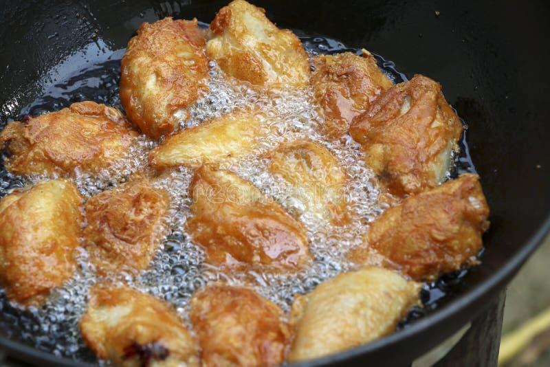 Pollo fritto in una pentola con olio caldo fotografia stock libera da diritti