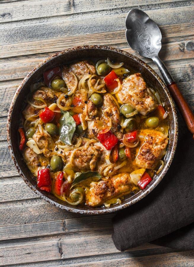 Pollo lento de la cocina con las aceitunas y las pimientas dulces en la cacerola en el fondo de madera, visión superior fotografía de archivo libre de regalías