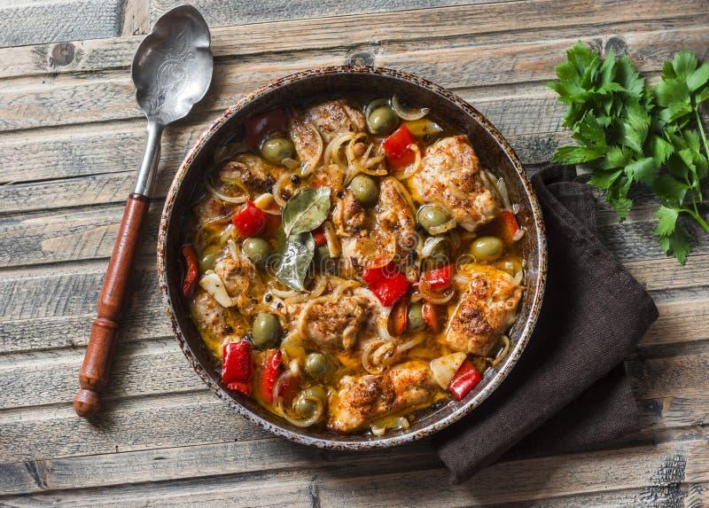Pollo lento de la cocina con las aceitunas y las pimientas dulces en la cacerola en el fondo de madera, visión superior fotos de archivo libres de regalías