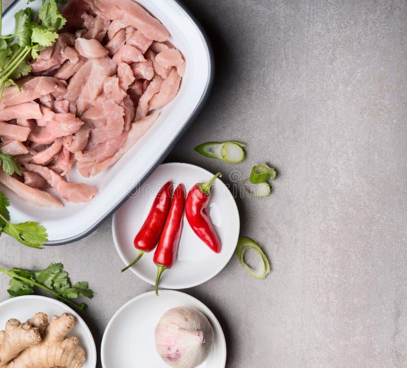 Pollo o carne di tacchino affettata con le spezie e condimento fresco per la dieta pulita che cucina sul fondo concreto grigio, v fotografia stock libera da diritti