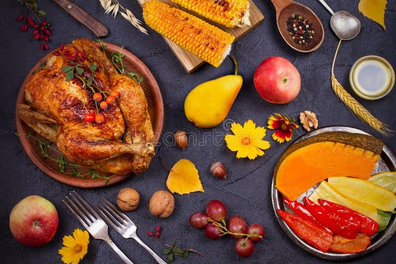 Pollo o pavo entero, frutas y verduras asadas a la parrilla del otoño: maíz, calabaza, paprika Concepto de la comida del día de l imagenes de archivo