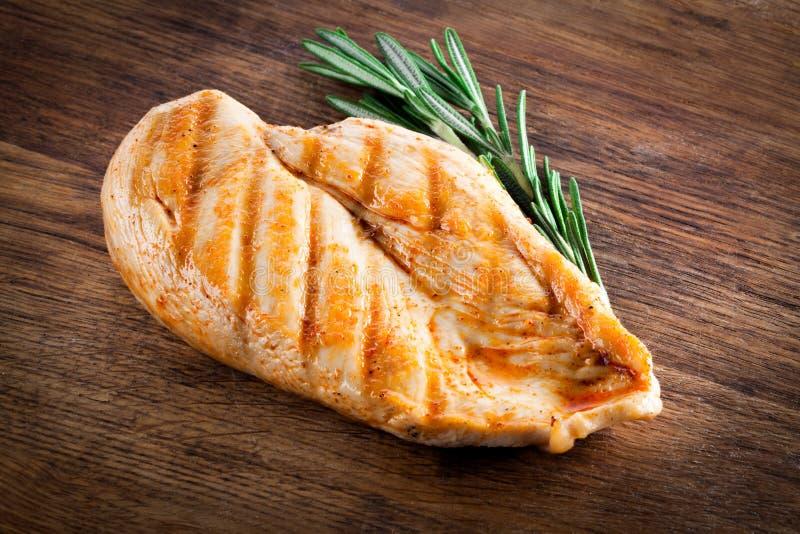 Pollo organico cotto con rosmarino su legno fotografia stock