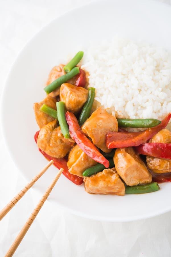 Pollo picante con las verduras (habas verdes y pimienta roja) y el arroz fotografía de archivo