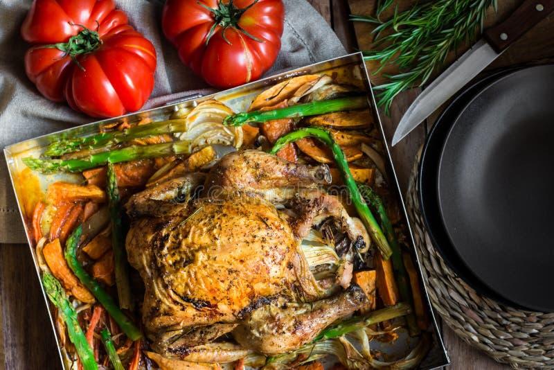 Pollo relleno asado hecho en casa con las zanahorias de las verduras, patatas dulces, espárrago, cebollas, romero foto de archivo libre de regalías