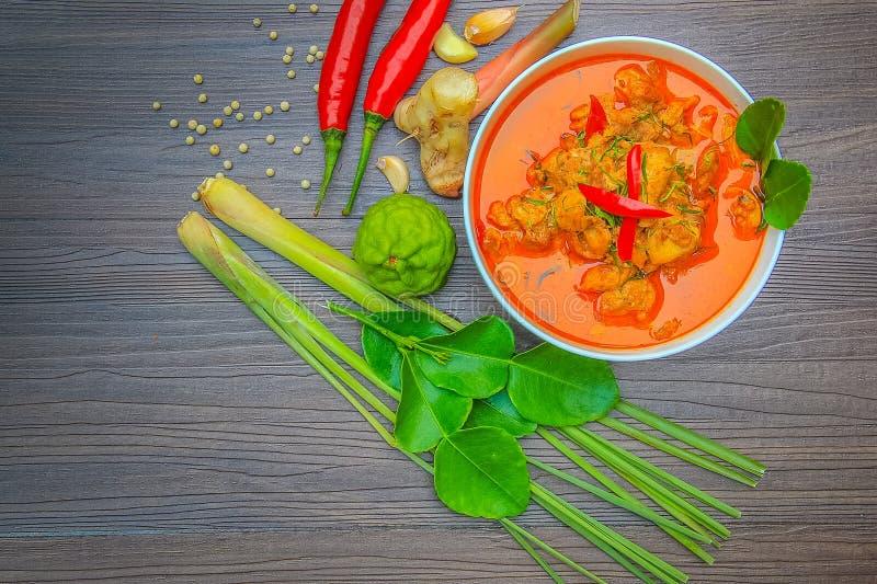Pollo rosso del curry, alimento piccante tailandese ed ingredienti freschi dell'erba sulla vista superiore di legno/natura morta, fotografia stock