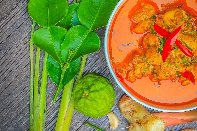Pollo rosso del curry, alimento piccante tailandese ed ingredienti freschi dell'erba sulla vista superiore di legno/natura morta, fotografie stock libere da diritti
