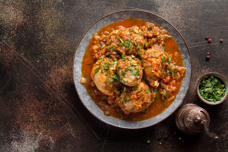 Pollo in salsa al pomodoro con le erbe e le cipolle, menta del prezzemolo del coriandolo, chakhokhbili orientale tradizionale del fotografia stock