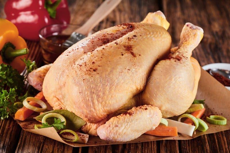 Pollo sazonado crudo entero con las verduras frescas imagenes de archivo